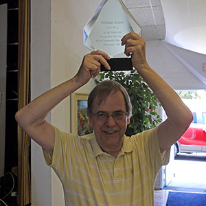 Bill Grant holds his Emerald life master award over his head