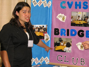 Felicia Massey points to the Chula Vista highschool bridge club poster